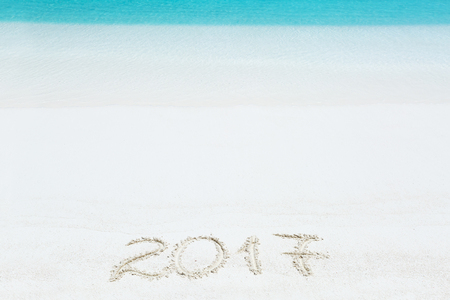 2017 inscription written on sandy beach, New Year greeting card