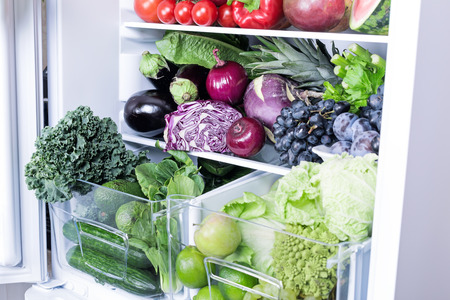 Opened refrigerator full of vegetarian healthy food, vibrant colour vegetables and fruits inside on fridge Banque d'images