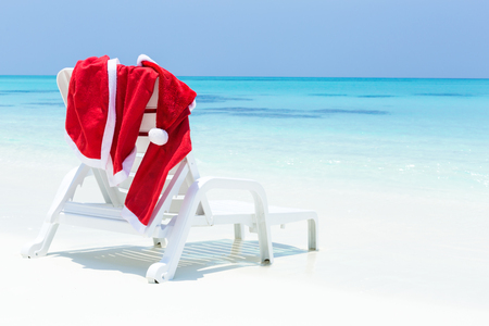 Santa Claus costume hanging on sunbed, close to sea and beach, nobody. Christmas holidays on tropical destinations