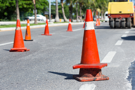 Road construction works. Traffic cones at tropical street warning about asphalt pavement works