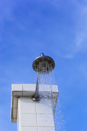 Water drops falling from a shower outside against blue sky