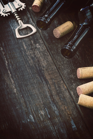 Bottle of wine,  corks and corkscrew on wooden background  Reklamní fotografie