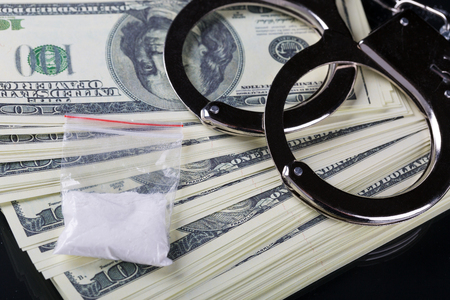 Handcuffs on dollar banknotes fan and cocaine, black background  Stock Photo