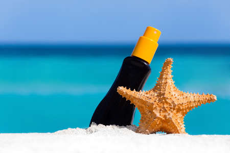 Sunscreen protection cream and starfish on white sand against turquoise caribbean sea water. Tropical summer vacation concept