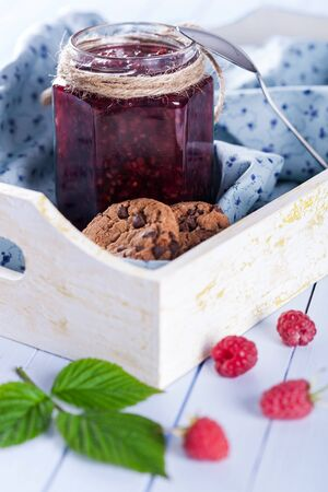 Homemade raspberry jam in jar and tasty cookies in wooden tray decorated with fresh berries and green leaves on table, selective focus