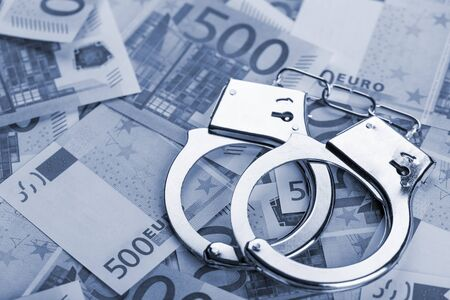 Pair of handcuffs closeup on euro banknotes background. Corruption problem in the world