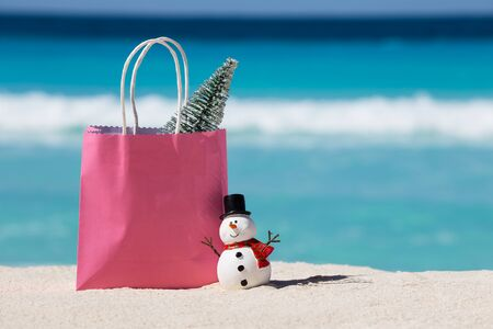 Snowman toy and pink gift paper bag with fir tree at white sandy beach on Caribbean sea background. Christmas celebration