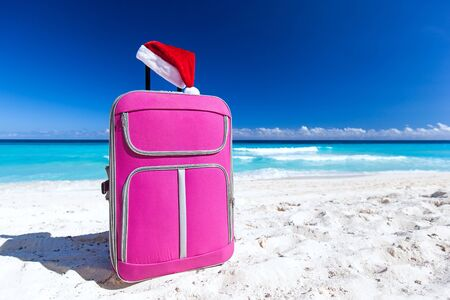 Christmas Santa Claus red hat on handle travel luggage with tropical beach and turquoise sea background. New Year holidays concept Stock Photo