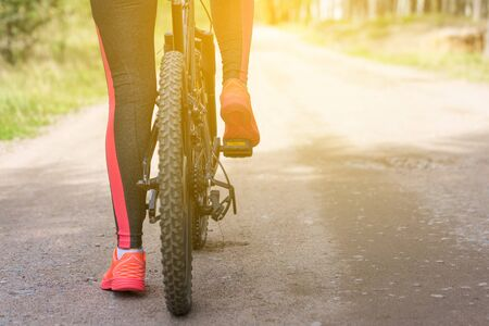 Woman riding a mountain bicycle along path at the forest. Closeup on pedal and foot. Healthy lifestyle and sport concept