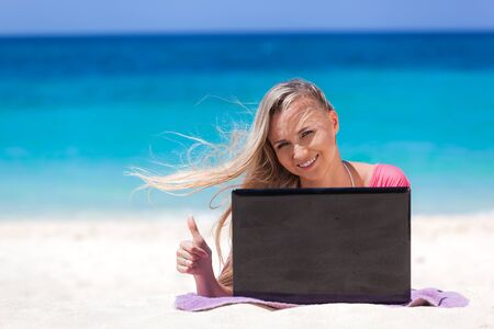 Blond girl with a laptop on tropical beach, freelance concept.