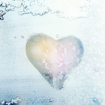 Heart shape symbol drawn on winter iced frozen window glass, macro frosty ornament, romantic Valentines Day background