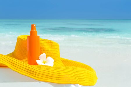 Beach accessories for healthy lifestyle and skin care, summer hat and sunblocker lotion on sunbed close to sea, cosmetics for sun protection concept, nobody