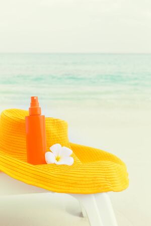 Beach accessories for healthy lifestyle and skin care, summer hat and sunscreen lotion on sunbed close to sea, cosmetics for sun protection concept, nobody, toned image Stock Photo