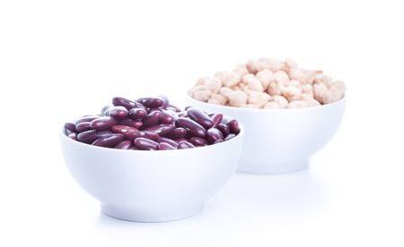 Raw dry chickpeas and red beans in bowl on white background, healthy vegan food with a lot of protein