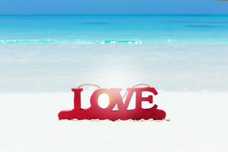 Valentines day greeting card, red wooden letters LOVE on sandy beach, honeymoon vacation background, copy space