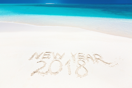 Handwritting inscription word NEW YEAR and numbers 2018 on perfect tropical sandy beach, travel vacation concept card for winter holidays