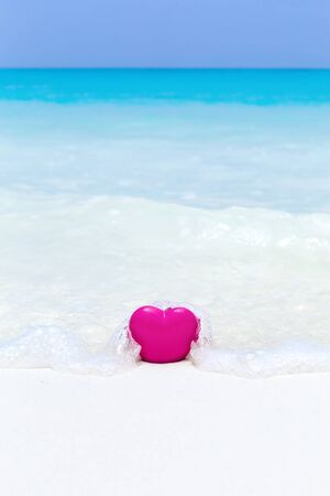 Valentines day concept greeting card, red heart on pristine sandy beach, honeymoon vacation background