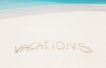 Handwritting inscription word VACATION on perfect tropical bounty beach, travel concept card for vacations