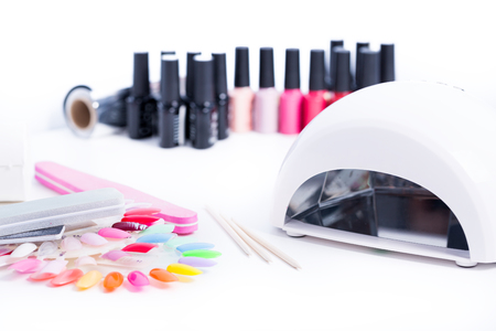 Manicure set  for gel nail procedure - Nail LED lamp, colour gel polishes and pink file on white table Stock Photo