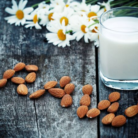 Glass of organic vegan nut almond milk on wooden table with word raw , decorated fresh camomile flowers. Healthy food concept Stock Photo