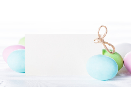 Paper blank tag decorated colorful pastel easter eggs on rustic wooden white background, Happy Easter cards with copy space for your text, mock up