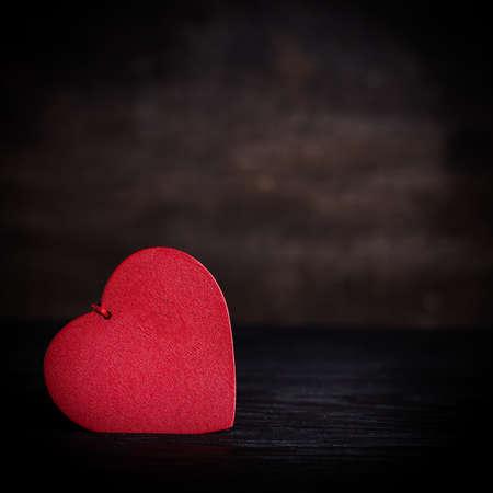St. Valentine concept decoration card. Red heart shape on dark wooden background, shallow depth