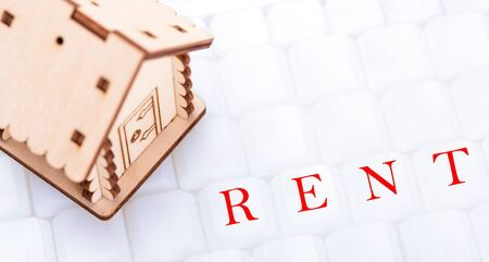 Real estate and property concept. Wooden model of house on white keyboard with sign RENT, closeup