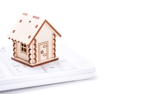 Real estate and property concept. Wooden model of house on white computer keyboard  Stock Photo