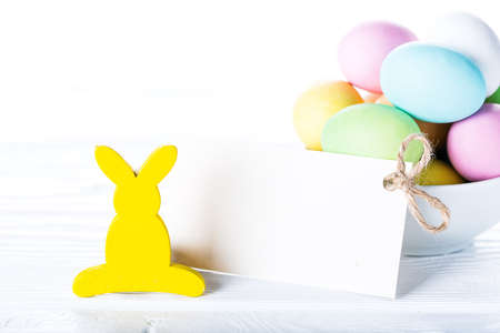 Colorful pastel easter eggs in bowl with blank paper tag for text, decorated yellow rabbit on white wooden background, Happy Easter card Stock Photo