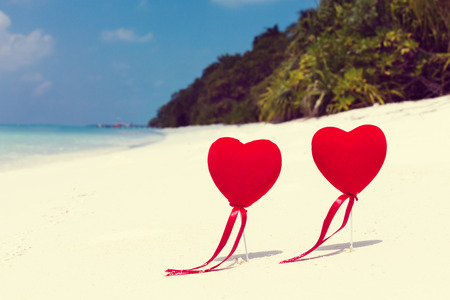 Red Hearts shape decoration on sandy tropical beach close to azur sea, St. Valentines day greeting card, travel background