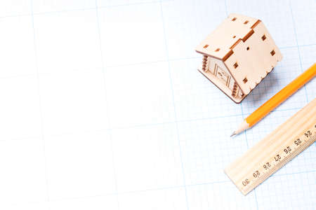 Planning design of new project. Wooden model of house, pencil and ruler on plotting paper  Stock Photo
