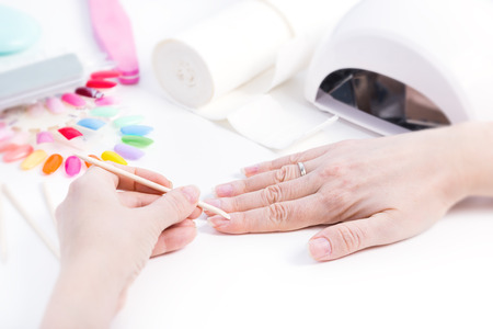 Gel nail procedure - Woman doing manicure with wooden stick on white table