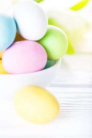 Colorful pastel easter eggs on rustic wooden white background, decorated rabbit and flowers. Happy Easter card Stock Photo