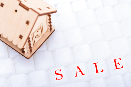 Real estate and property concept. Wooden model of house on white keyboard with sign SALE, closeup