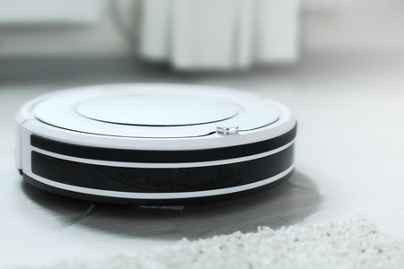 White robotic vacuum cleaner on laminate floor cleaning dust in living room interior. Smart electronic housekeeping technology Foto de archivo - 96845929