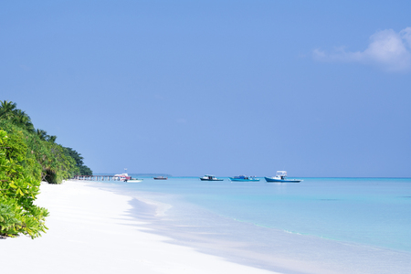 Perfect wild sandy Maldives beach with speedboats shipping at the sea. Travel destinations