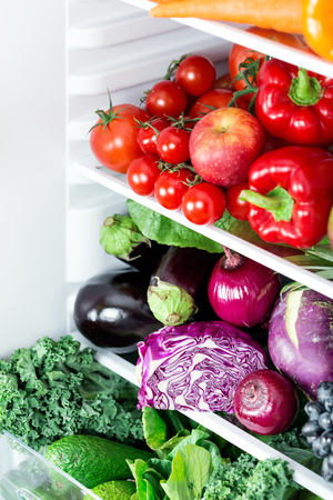 Opened refrigerator full of vegetarian healthy food, vibrant colour vegetables and fruits inside on fridge, focus on red cabbage