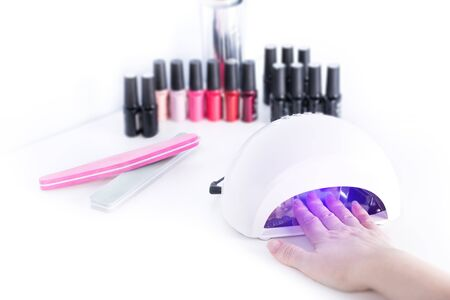 Gel nail procedure - Woman drying neils in Led Lamp on white table