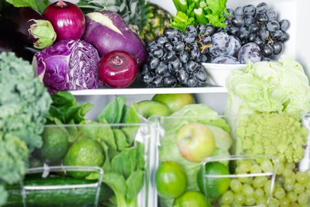 Opened refrigerator full of vegetarian healthy food, vibrant colour vegetables and fruits inside on fridge Stock Photo