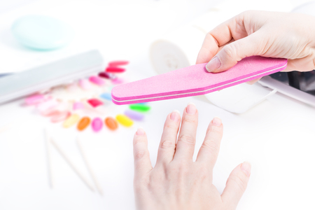 Gel nail procedure - Woman doing manicure with pink file on white table