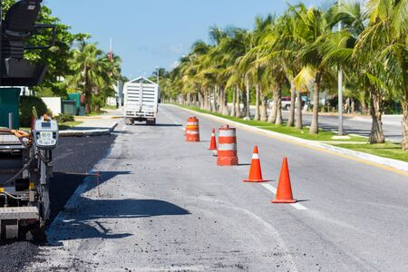 Pavement truck laying fresh asphalt  during tropical road construction