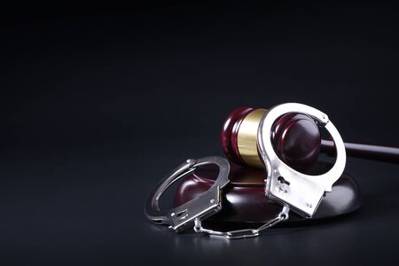 Wooden judge gavel and police handcuffs isolated on black background  Stock Photo