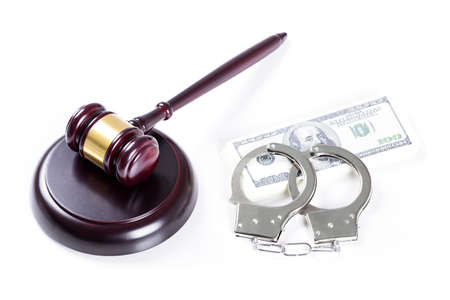 Wooden judge gavel and police handcuffs on hundred dollar banknotes stack isolated over white background