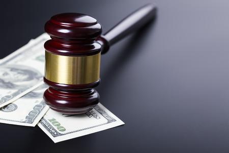 Wooden judge gavel on hundred dollar banknotes closeup over black background