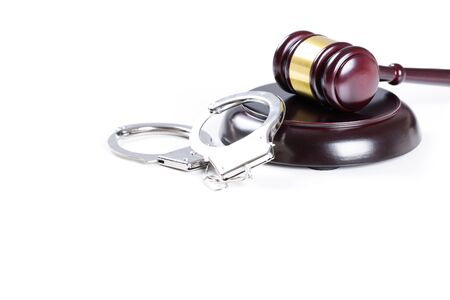 Wooden judge gavel and police handcuffs isolated on white background