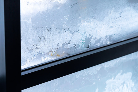 Winter iced pattern on frozen window glass, bad ventilation concept, cold temperature outside