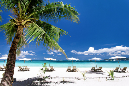 Sun umbrellas and chairs on tropical beach, Philippines, Boracay Stock Photo