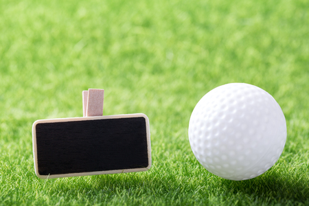 White golf ball and mockup board on green grass background, closeup  Stock Photo