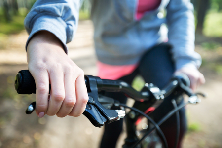 Woman riding a mountain bicycle along path at the forest. Closeup on handlebar with female hand. Healthy lifestyle and sport concept Stock Photo