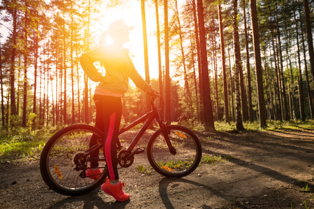 Woman riding a mountain bicycle along path at the forest. Healthy lifestyle and sport concept